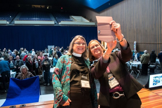 Bishop Mary and Bishop Elect Lucinda Ashby take selfie with the audience at Convention