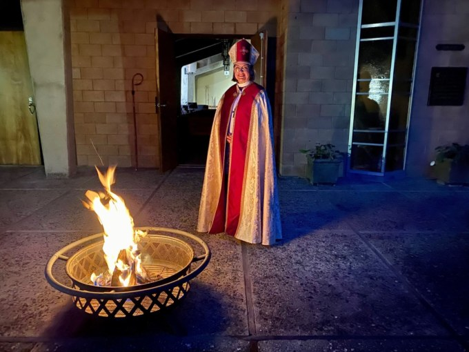 Bishop Lucinda standing near fire in fire pit at Good Shepherd church